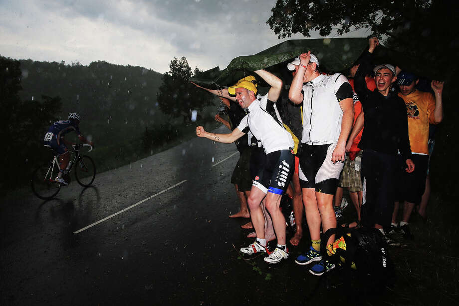 Cycling fans encourage the riders in the poor weather conditions during stage seventeen of the 2013 Tour de France, a 32KM Individual Time Trial from Embrun to Chorges, on July 17, 2013 in Chorges, France. Photo: Doug Pensinger, Getty Images / 2013 Getty Images