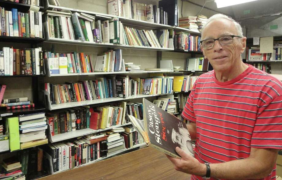 "Dick Lowenstein, a longtime volunteer at the Westport Library, holds a book titled ""Casey Stengel's Secret,"" one of about 80,000 books and other items that will be available at the library's book sale this weekend. Photo: Meg Barone / Westport News contributed"