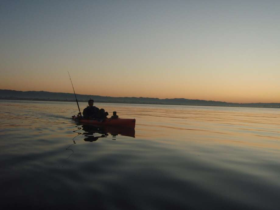 Chuck Espirtu paddles out at dawn across San Francisco Bay at dawn.