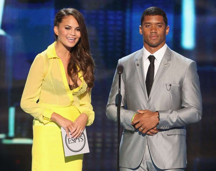 Model Chrissy Teigen and Seahawks quarterback Russell Wilson present an award.