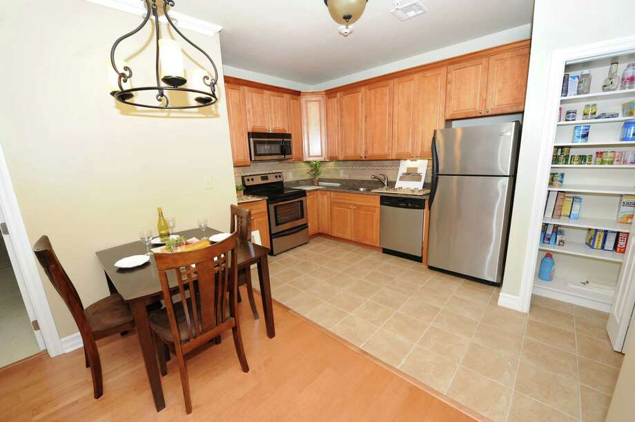 The kitchen and dining area of a model condo in The Bentley condominiums on Tuesday, July 16, 2013 in Clifton Park, N.Y. People can rent or own a condo here. (Lori Van Buren / Times Union) Photo: Lori Van Buren / 00023190A