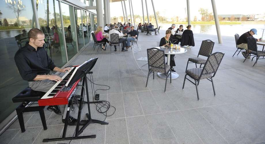 Caleb Fontenot, left, a Lamar University music major provided the entertainment over the centre's audio system.  Monday November 19, 2012 was the first of three scheduled Lunch at the Lake events at the new downtown Event Centre. The City of Beaumont provided the music, seating, and scenery, and visitors could get lunch from one of these food vendors that were on site like Big Bo's barbecue, Charles Brewer barbecue, Rao's pizza and gelato, Terrell's ice cream, Wise Guys Grill burgers and fries, and Zummo's sausage and boudain. Others even ordered in advance from Katharine & Co. for their lunches.  Dave Ryan/The Enterprise