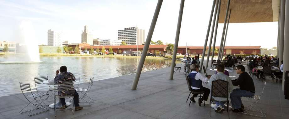 Some of the lunch diners enjoyed the shade offered by the centre's giant awning and the view of the city.  Monday November 19, 2012 was the first of three scheduled Lunch at the Lake events at the new downtown Event Centre. The City of Beaumont provided the music, seating, and scenery, and visitors could get lunch from one of these food vendors that were on site like Big Bo's barbecue, Charles Brewer barbecue, Rao's pizza and gelato, Terrell's ice cream, Wise Guys Grill burgers and fries, and Zummo's sausage and boudain. Others even ordered in advance from Katharine & Co. for their lunches.  Dave Ryan/The Enterprise