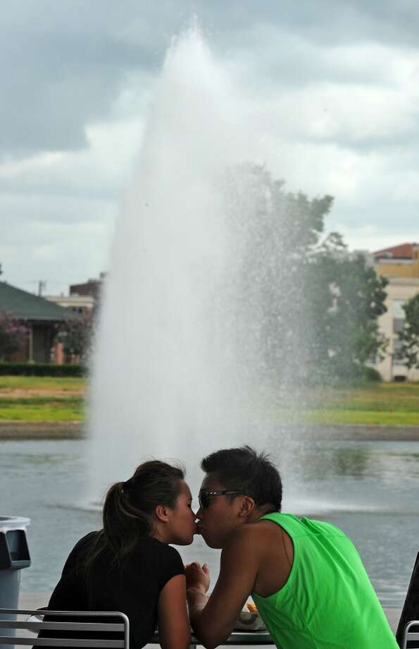 Steven Hoang kisses Vicki Pham next to the downtown fountain during Lunch at the Lake on Monday.  Photo taken Monday, July 08, 2013 Guiseppe Barranco/The Enterprise
