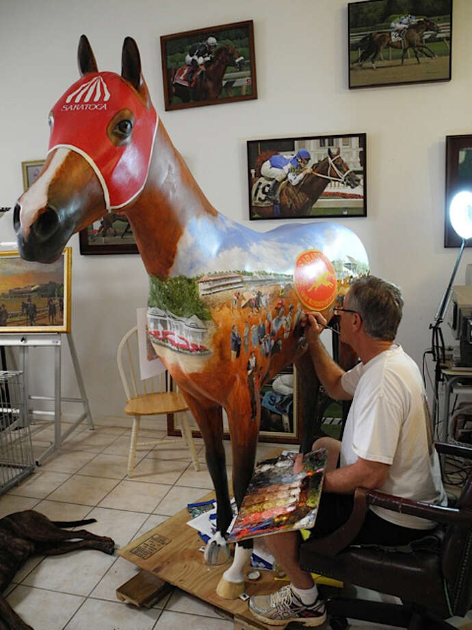 Robert Clark of Indian Harbour Beach, FL, paints the fiberglass horse he designed and painted in honor of the 150th anniversary season at Saratoga Race Course.