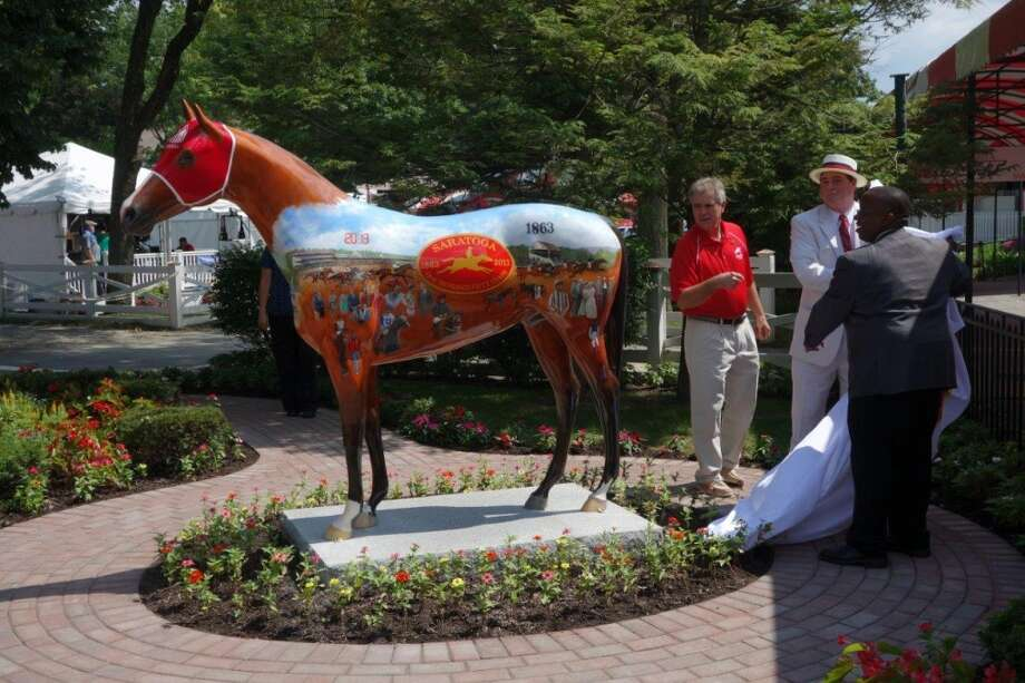 From left, artist Robert Clark, Saratoga 150 Honorary Chair John Hendrickson and NYRA Vice President and Chief Marketing Officer Rodnell Workman unveil the equine art piece in honor of the 150th anniversary season at Saratoga Race Course on Thursday, July 18.