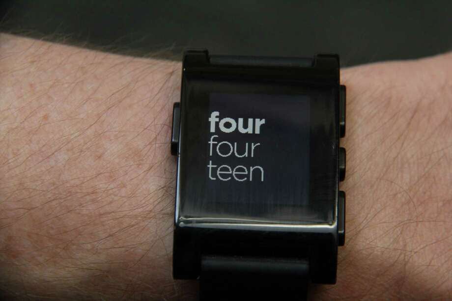 This photo taken July 16, 2013, shows the Pebble smart watch with customizable faces, this one showing the time written out in New York. The watch functions as an extension of the smartphone, a replacement for the ring signal whenever you get a call, text, email or calendar reminder. It also shows the first few lines of messages, so the wearer would know whether to fish out the phone for replies. (AP Photo/Anick Jesdanun) Photo: Anick Jesdanun, Associated Press / Associated Press