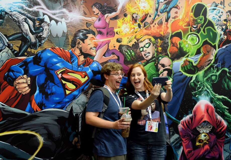 Ryan Garafola (L) and Libby Foulk, both of Arizona, take a photo in front of a DC Comics mural at Comic-Con International 2013 at the San Diego Convention Center on July 17, 2013 in San Diego, California.  (Photo by Ethan Miller/Getty Images)