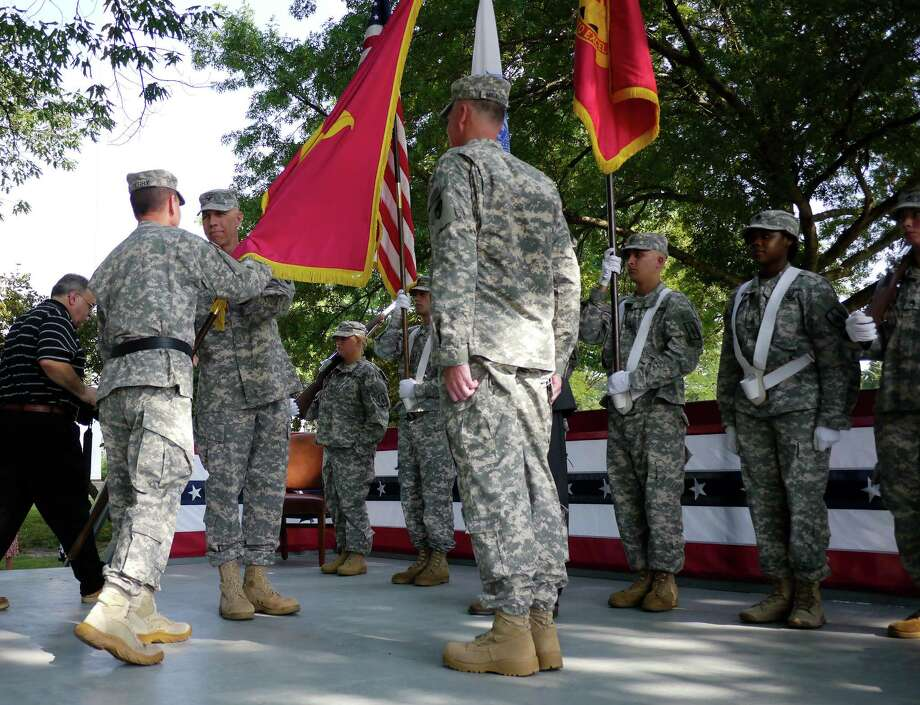 Maj. Gen. Michael Terry, left, the commanding general of TACOM Life Cycle Management Command, hands the Arsenal's organizational colors to incoming commander, Col. Lee Schiller Jr., as outgoing commander Col. Mark  Migaleddi, right, looks on during the 58th Change of Command Ceremony at the Watervliet Arsenal on Thursday, July 18, 2013, in Watervliet, NY.    (Paul Buckowski / Times Union) Photo: Paul Buckowski / 00023224A