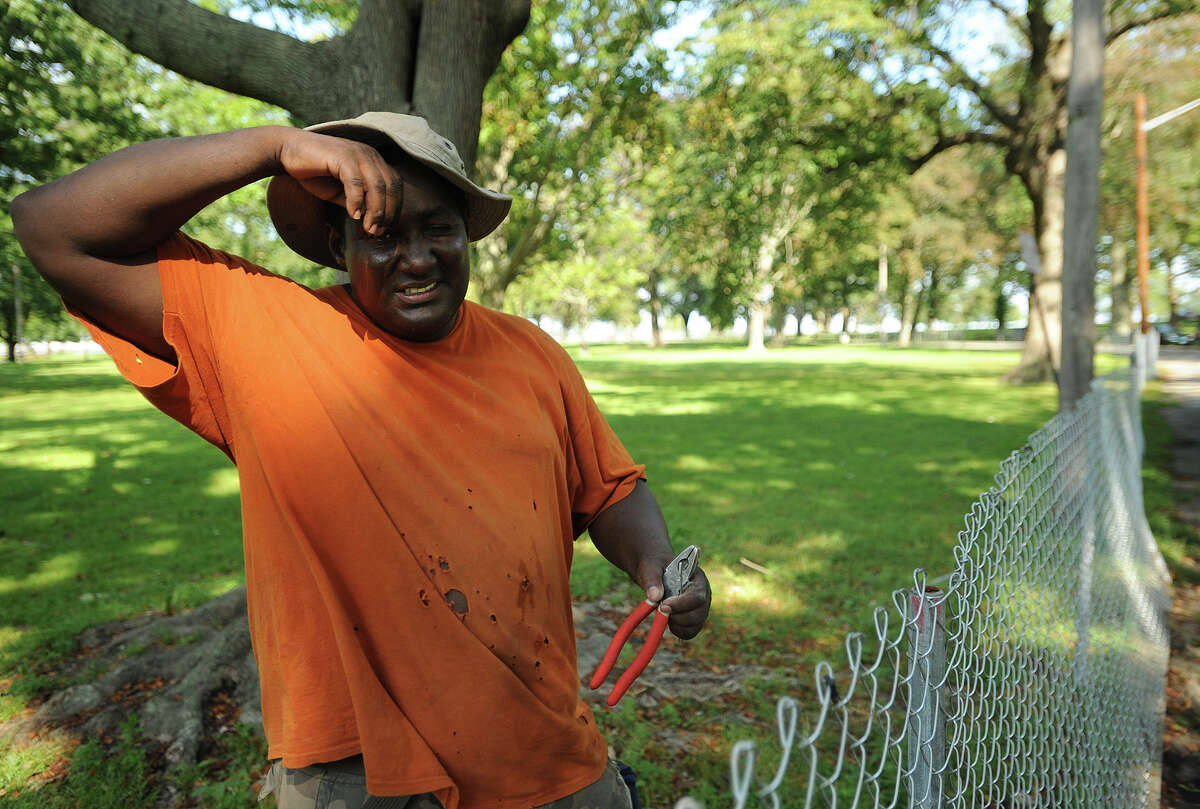 Francisco Rosario of Bridgeport wipes his brow as he works in the extreme heat installing temporary fencing for The Gathering of the Vibes music festival at Seaside Park in Bridgeport, Conn. on Monday, July 15, 2013.
