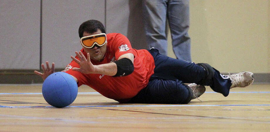Goalball player Paul Heidhues dives to block the ball from the goal during a team scrimmage of goalball at Morgan's Wonderland on Tuesday, July 16, 2013. Heidhues is part of a local team overseen by South Texas Regional Adaptive Paralympic Sports (STRAPS). The team is expected to compete against others in the fall according to STRAPS director Wendy Gumbert. Photo: Kin Man Hui, San Antonio Express-News / ©2013 San Antonio Express-News