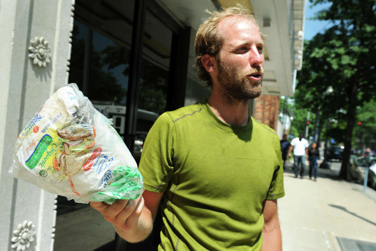 Rob Greenfield speaks during an interview in Bridgeport, Conn., July 18, 2013. The bag he holds contains all of the trash he has produced on his bicycle trip from San Francisco to Waitsfield, Vt., a journey of roughly 4,500 miles. Calling his trip Off the Grid Across America, it is meant to promote his lifestyle of environment awareness and adventure.