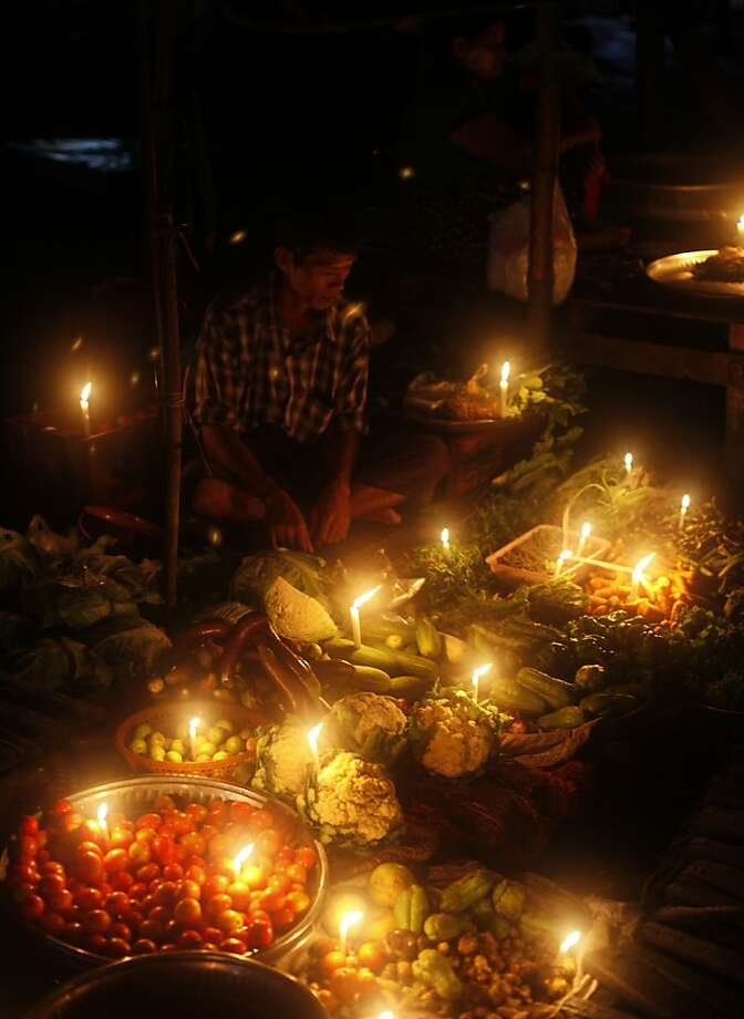 Locally grown and romantically lit: A vendor sells produce by candlelight at a street market in Yangon, Myanmar. Photo: Khin Maung Win, Associated Press