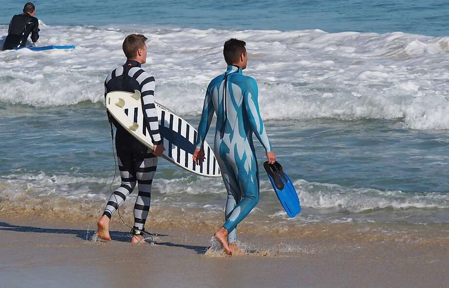 Sharks hate the taste of zebra: In Perth, Australia, a surfer and a diver wear the two styles of Shark Attack Mitigation Systems' wetsuits. The new technology presents the wearer as potentially dangerous and unpalatable to a shark (left) or difficult to see underwater (right). Photo: Shark Attack Mitigation Ststems, AFP/Getty Images