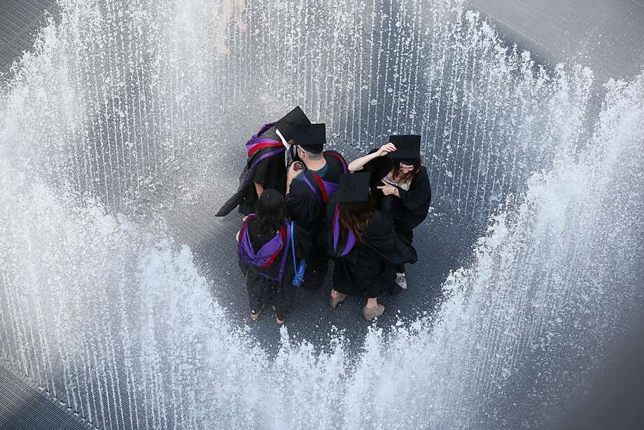 Cap and drown:New graduates seek relief in a fountain after receiving their diplomas at the Royal Festival Hall in London. Like much of the United States, England is suffering through an oppressive heat wave. Photo: Oli Scarff, Getty Images