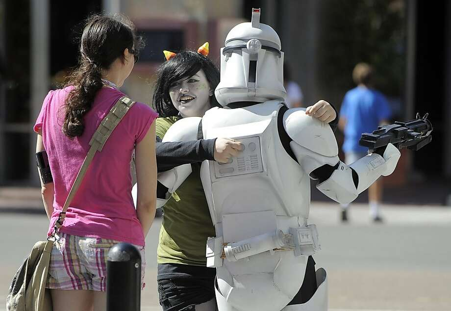 The Empire steps out: An admirer gives an Imperial Storm Trooper a big hug in front of his date at Comic-Con in San Diego. Photo: Chris Pizzello, Associated Press