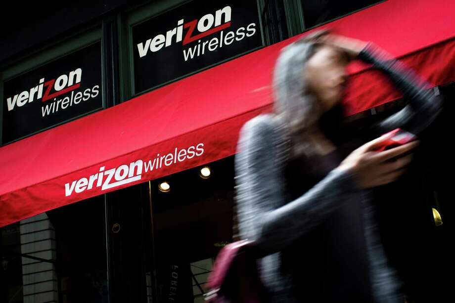 FILE - In this Thursday, June 6,  2013, file photo, a pedestrian uses her cell phone as she passes a Verizon Wireless store on Broadway in Lower Manhattan, in New York.  Verizon Communications Inc. reports quarterly financial results before the market opens on Thursday, July 18, 2013.  (AP Photo/John Minchillo, File) ORG XMIT: NYBZ168 Photo: John Minchillo / FR170537 AP