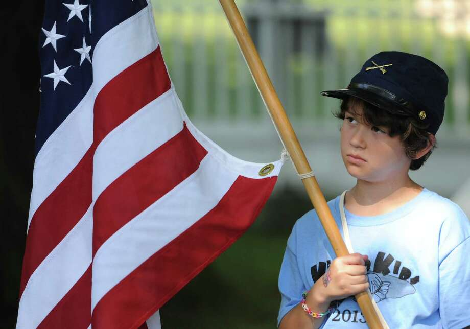 Aaron Cohen, 9, of Ridgefield, holds an American flag while leading a march at the Keeler Kids summer camp program at the Keeler Tavern Museum in Ridgefield, Conn. on Thursday, July 18, 2013.  The camp, for children grades four through six, had a localized Civil War theme, incorporating historic-themed activities like marching, quill pen letter writing, button making and cooking authentic age foods. Photo: Tyler Sizemore / The News-Times