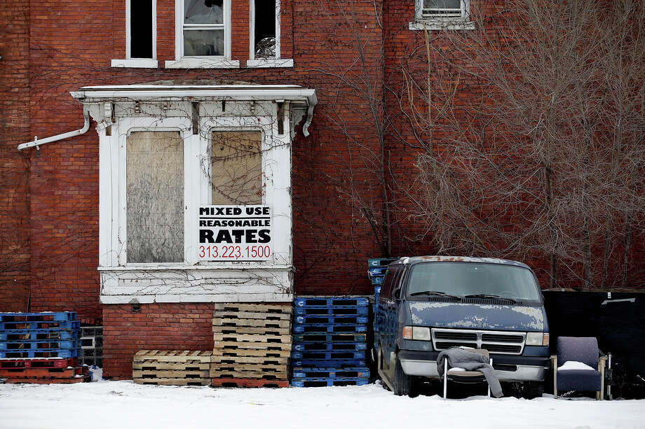 A sign advertising building rates is seen on an abandoned building on February 24, 2013 in Detroit, Michigan. The city of Detroit has faced serious economic challenges in the past decade, with a shrinking population and tax base while trying to maintain essential services. Photo: J.D. Pooley, Getty Images / 2013 Getty Images
