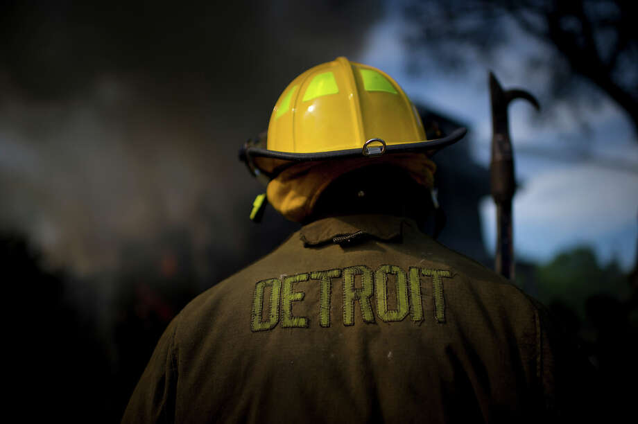 "A firefighter stands by as his co-workers attempt to extinguish a blaze at the abandoned duplex at 2645/51 Frederick Street in Detroit's east end. The ""black bottom"" area of Detroit has become a literal hot bed of arson attacks this month. The fire was the first of three on the same day. Photo: Lucas Oleniuk, Toronto Star Via Getty Images / Toronto Star"