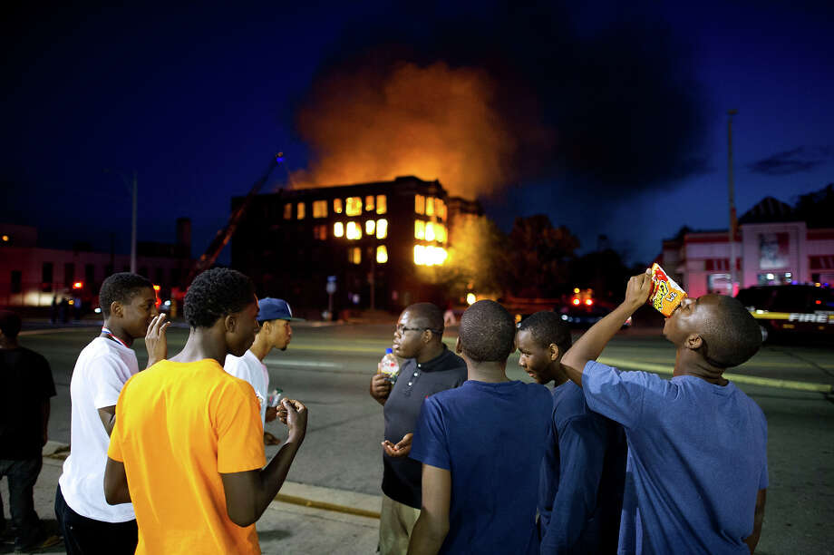 Two abandoned apartment buildings burn on Waverly Street in the declining Detroit neighborhood of Highland Park while bystanders pay little attention to the all to common occurrence. Photo: Lucas Oleniuk, Toronto Star Via Getty Images / Toronto Star