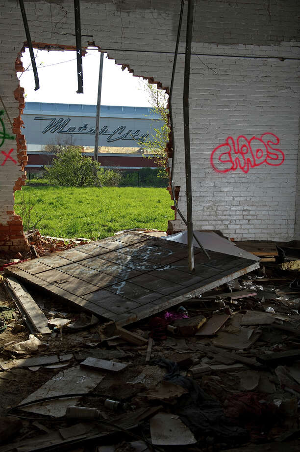 The Motor City Casino and hotel is seen through a hole in the wall of an abandoned building along Grand River Avenue on May 1, 2013 in Detroit, Michigan. The casino building incorporated Wagner Baking Company, a historic Detroit landmark. Photo: Christian Science Monitor, Christian Science Monitor/Getty  / 2013 The Christian Science Monitor