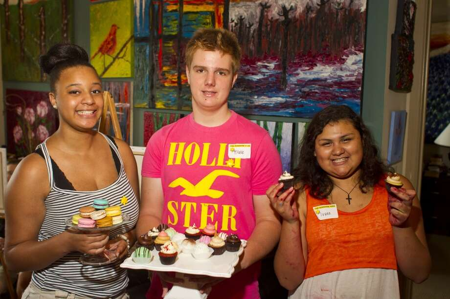Alexis Walker, 15, left, Blake Bolin, 14, center and Ivana Camarillo,14, hold snacks donated by Petite Sweets ,