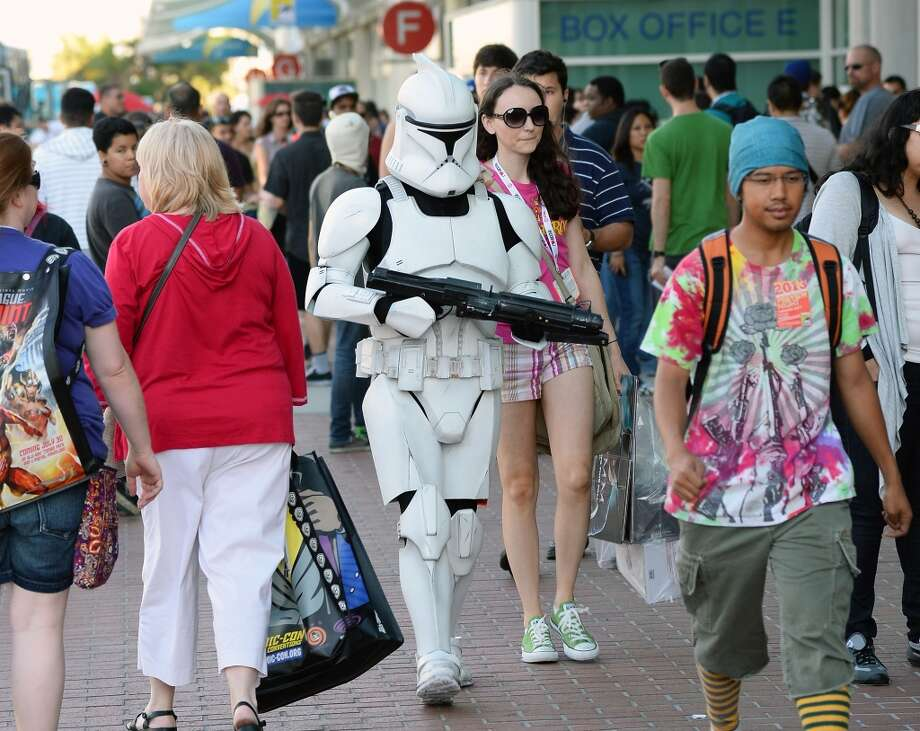 "Myke Soler (C) of California walks outside the San Diego Convention Center dressed as a clone trooper from the ""Star Wars"" movie franchise with his wife Kimberly Soler during Comic-Con International 2013 on July 17, 2013 in San Diego, California."