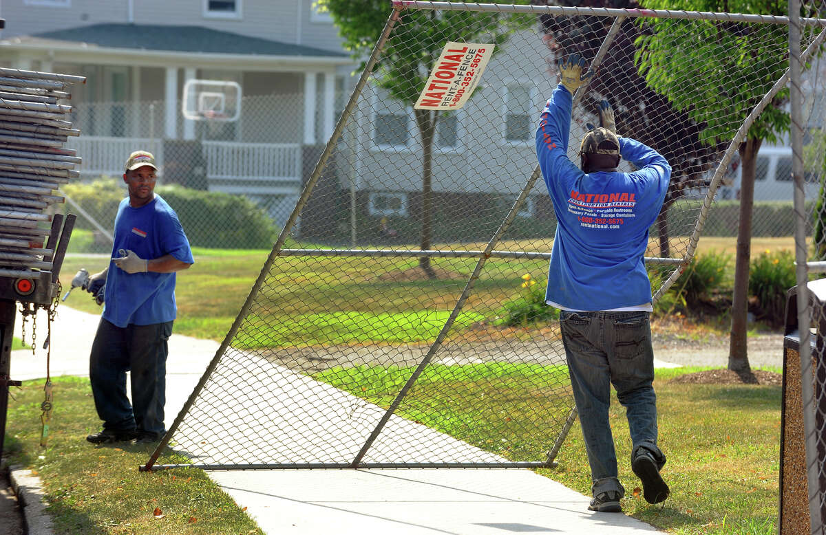 National Construction Rentals employees Miguel Frias and Francisco Stephens, left, erect fencing in preparation for the upcoming Vibes Concert at Seaside Park along Broad Street in Bridgeport, Conn. on Thursday July 18, 2013.