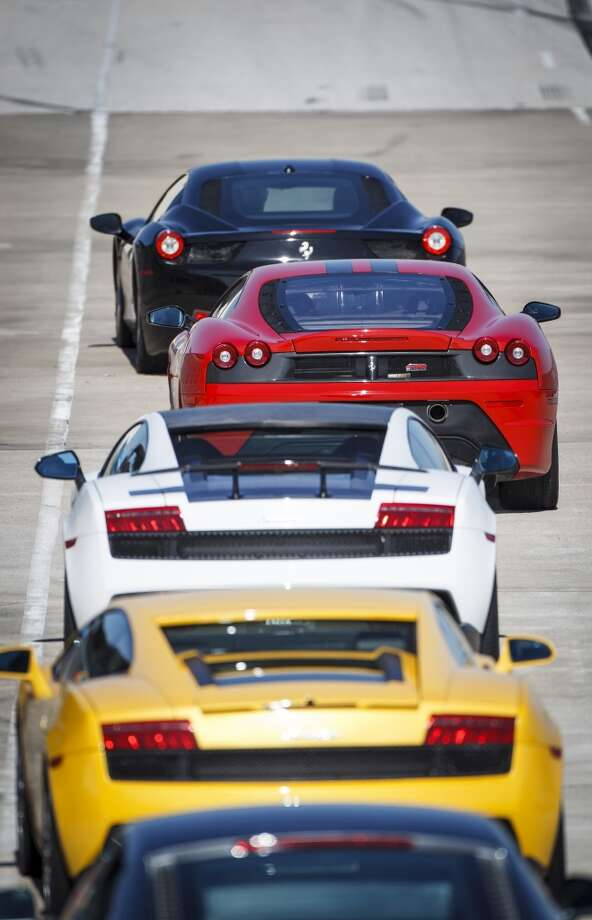 A selection of high-end sports race cars wait to be driven at the Exotic Driving Experience at MSR race track in Angleton.  ( Michael Paulsen / Houston Chronicle )