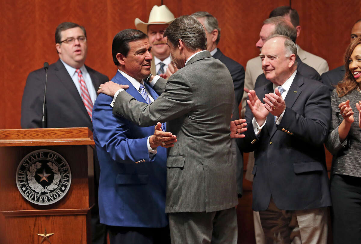 Again wearing his blue coat, State Sen. Eddie Lucio D-Brownsville, greets Gov. Rick Perry before the signing into law of the abortions restrictions bill on July 18, 2013.