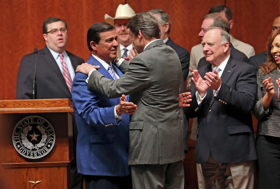 Again wearing his blue coat, State Sen. Eddie Lucio D-Brownsville, greets Gov. Rick Perry before the signing into law of the abortions restrictions bill  on July 18, 2013. Photo: Tom Reel, San Antonio Express-News