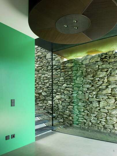 A vitreous staircase between a shell of stone wall and weathered shingles, leads to the down stairs