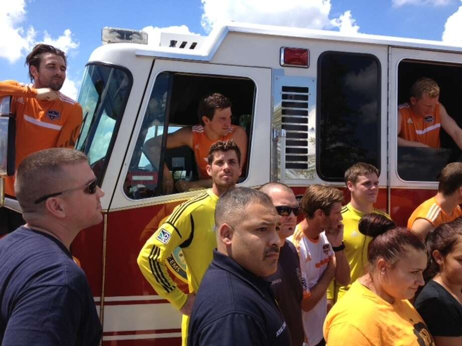 Dynamo players and firefighters from  Firehouses 51 and 68 gather for a photo on Thursday. (Jose de Jesus Ortiz/Houston Chronicle)