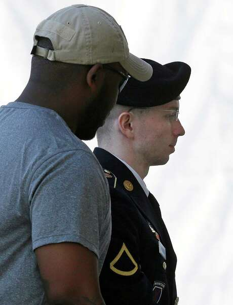 Army Pfc. Bradley Manning, right, who provided WikiLeaks with hundreds of thousands of classified U.S. documents, is escorted into his court-martial hearing in Fort Meade, Md., on Thursday. Photo: Patrick Semansky, STF / AP