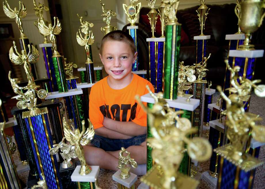 Antonio Sandalo, 7, sits surrounded by his numerous trophies in his Stamford home on Thursday, July 18, 2013. Sandalo will compete in the world amateur motocross championship in Tennessee. Photo: Lindsay Perry / Stamford Advocate