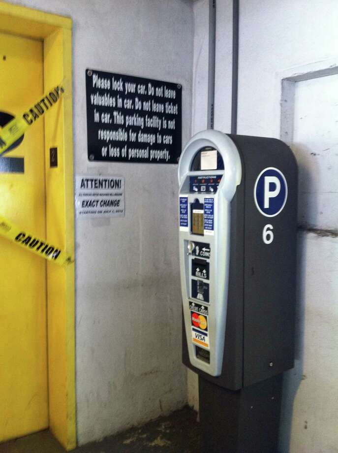 A small black and white sign taped to the wall to the left of a pay station in the Bell Street municipal garage in downtown Stamford tells visitors that the machine accepts exact change only. Photo: Angela Carella