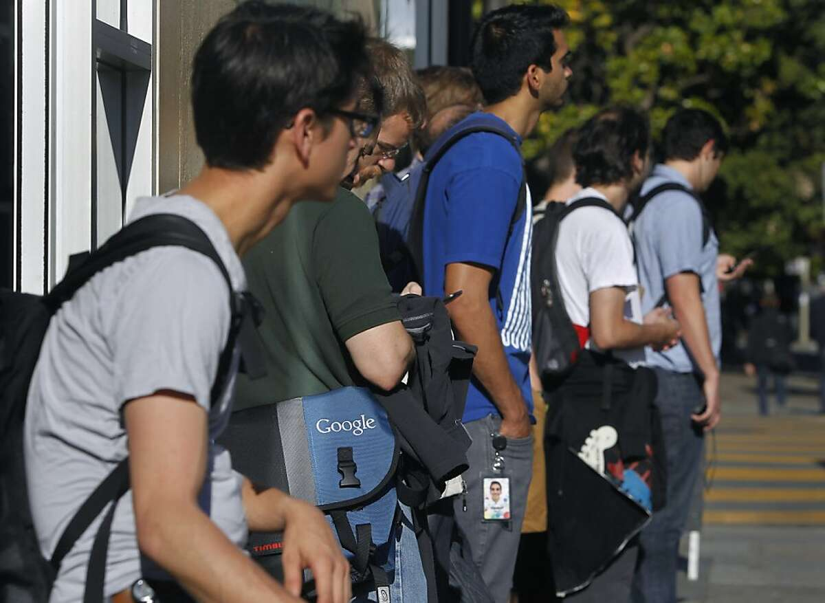 Google employees wait for a private shuttle bus at 18th and Dolores streets in San Francisco, Calif. that will transport them to their Silicon Valley workplace on Friday, June 14, 2013.