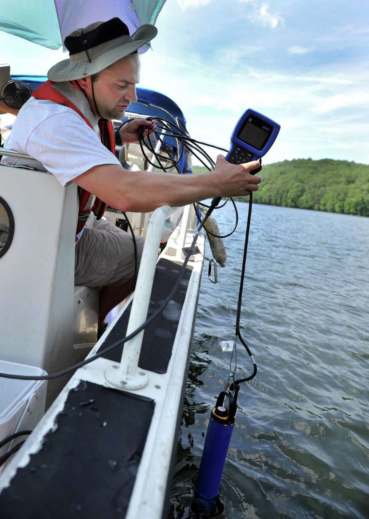 Joe Martin with US Geological Survey drops an instrument into the waters of Lake Lillinonah to test the water quality, Monday, July 15, 2013.