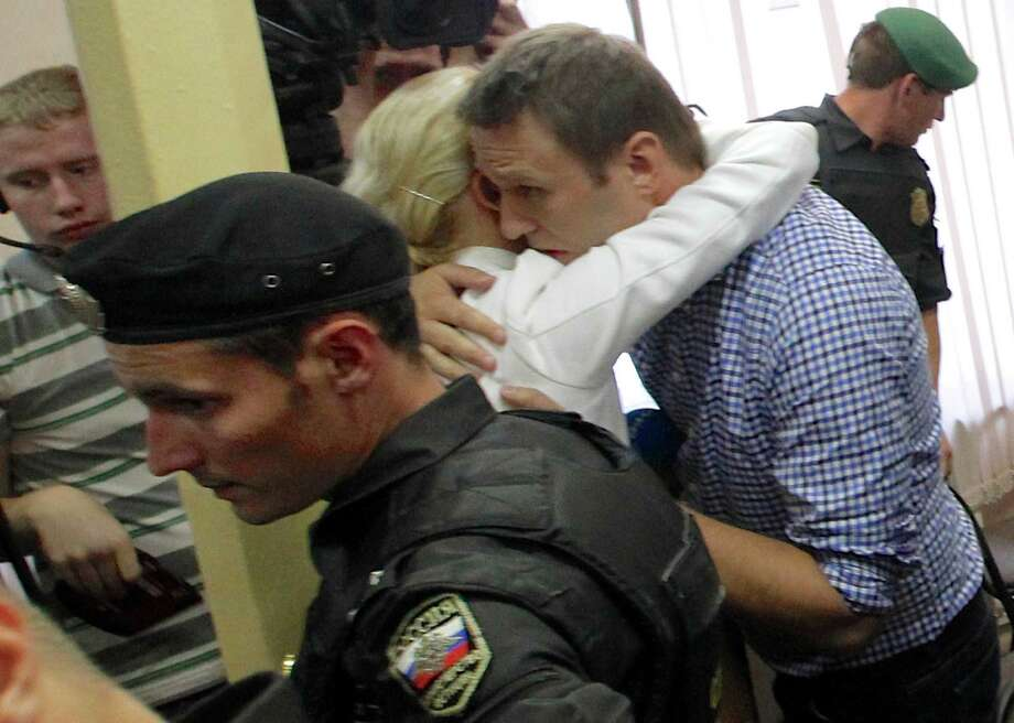 Russia's charismatic opposition leader Alexei Navalny embraces his wife, Yulia, at a court in Kirov, Russia, on Thursday after he was convicted of embezzlement and sentenced to five years in prison. Photo: Dmitry Lovetsky, STF / AP