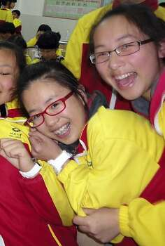 In this undated photo made available Monday, July 8, 2013, Ye Mengyuan, left,  and Wang Linjia, right, pose for photos with other classmates in the classroom in Jiangshan city in eastern China's Zhejiang province. Chinese state media and Asiana Airlines have identified the two victims of the Asiana Airlines crash at San Francisco International Airport girls as Ye Mengyuan and Wang Linjia, students in Zhejiang, an affluent coastal province in eastern China.  (AP Photo) CHINA OUT Photo: Associated Press