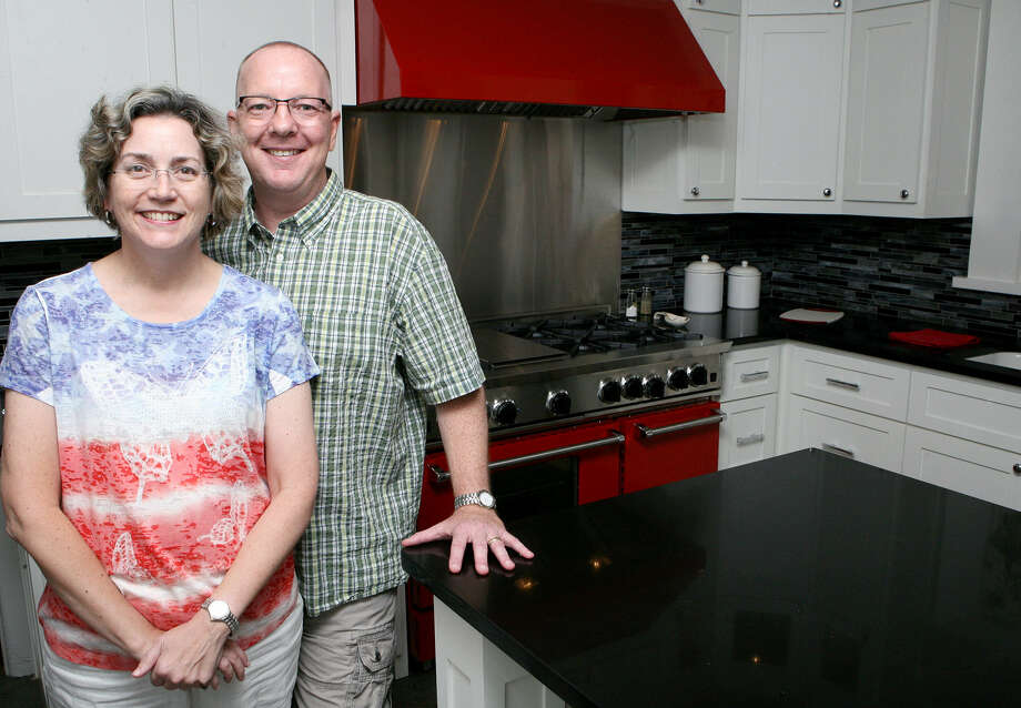 Beth and Bobby Dodd finished with the kitchen remodel early in July. The black-and-white color scheme is punched up with red accents and a sparkling chandelier above the island. Photo: Photos By Cynthia Esparza / For The Express-News