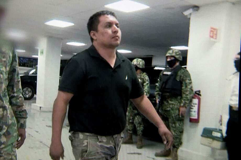Miguel Angel Trevino Morales is escorted by marines upon his arrival in Mexico City on Tuesday. Photo: HO, Handout / AFP