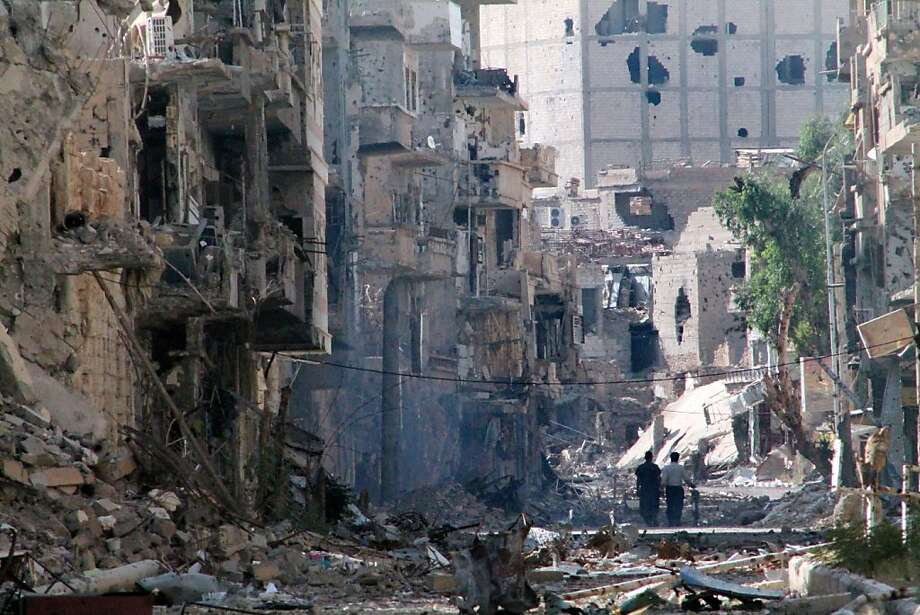 Syrians walk through the rubble of a destroyed street in Deir Ezzor. Photo: Ahmad Aboud, AFP/Getty Images