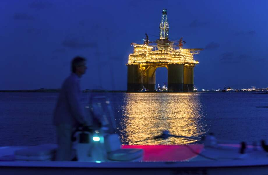 A boater passes the Royal Dutch Shell Plc Olympus tension leg platform (TLP) at dawn as it sets sail from Kiewit Offshore Services in Ingleside, Texas, U.S., on Saturday, July 13, 2013. Olympus, Shell's biggest constructed tension leg platform, started the ten day, 425-mile voyage to Mars B Field in the Gulf of Mexico on July 13. Photographer: Eddie Seal/Bloomberg Photo: Eddie Seal, Bloomberg