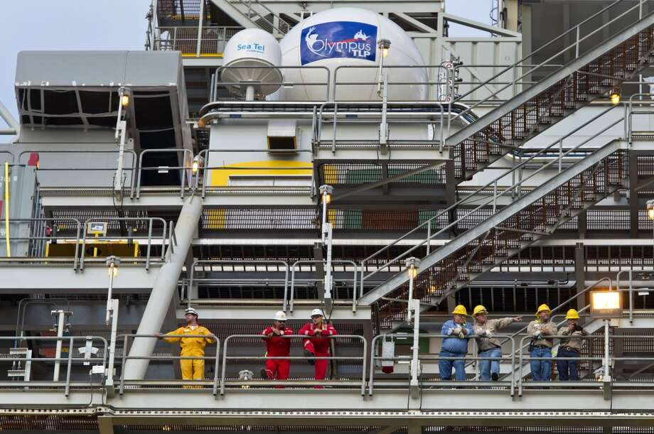 Workers stand aboard the Royal Dutch Shell Plc Olympus tension leg platform (TLP) as it sets sail from Kiewit Offshore Services in Ingleside, Texas, U.S., on Saturday, July 13, 2013. Olympus, Shell's biggest constructed tension leg platform, started the ten day, 425-mile voyage to Mars B Field in the Gulf of Mexico on July 13. Photographer: Eddie Seal/Bloomberg Photo: Eddie Seal, Bloomberg
