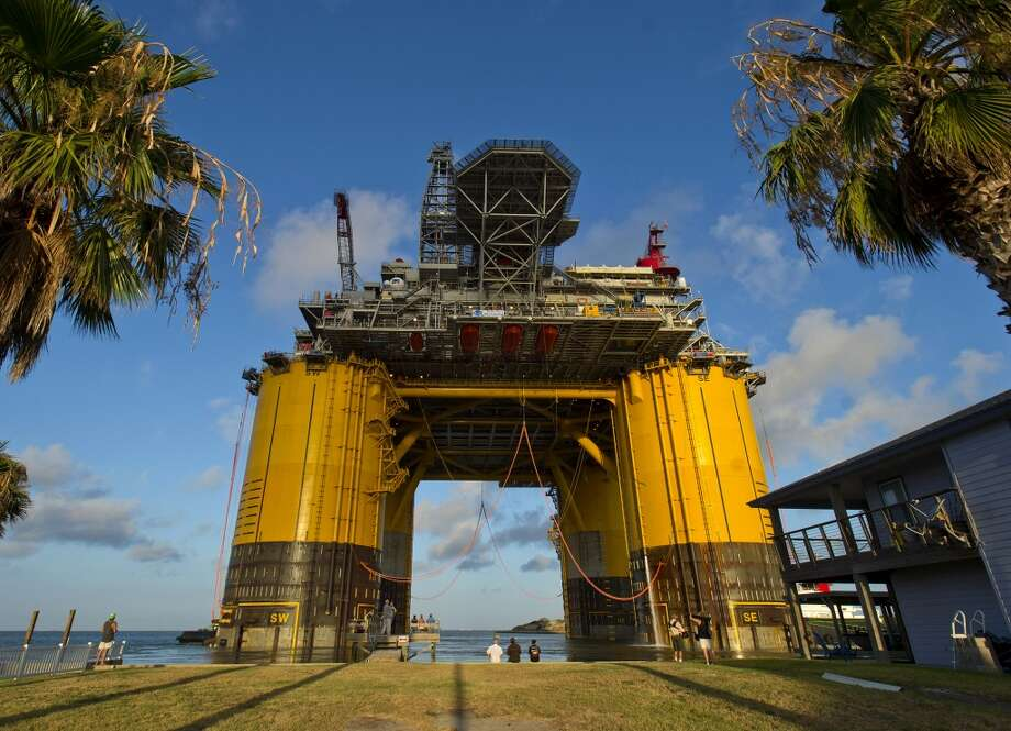 The Royal Dutch Shell Plc Olympus tension leg platform (TLP) sails from Kiewit Offshore Services past homes in Ingleside, Texas, U.S., on Saturday, July 13, 2013. Olympus, Shell's biggest constructed tension leg platform, started the ten day, 425-mile voyage to Mars B Field in the Gulf of Mexico on July 13. Photographer: Eddie Seal/Bloomberg Photo: Eddie Seal, Bloomberg