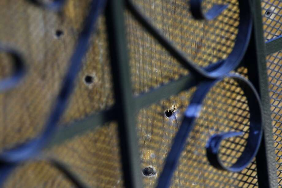 Bullet holes pierce the front door of the Oakland home where an 8-year-old girl was killed and three other people were hurt. Photo: Lacy Atkins, The Chronicle