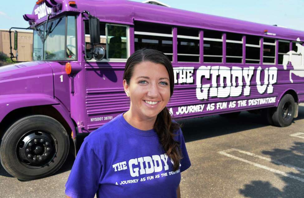 Tracy Cornwell with her bright purple bus called the Giddy Up, in the Colonie Center parking lot in Colonie, NY, Thursday July 18, 2013. She is running trips from Albany and Clifton Park to Saratoga Springs and Lake George. (John Carl D'Annibale / Times Union)