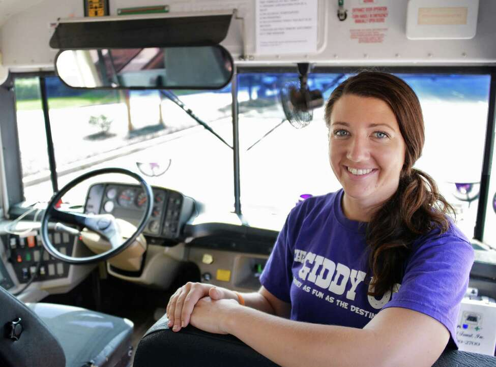 Tracy Cornwell inside her bright purple bus called the Giddy Up, in the Colonie Center parking lot in Colonie, NY, Thursday July 18, 2013. She is running trips from Albany and Clifton Park to Saratoga Springs and Lake George. (John Carl D'Annibale / Times Union)